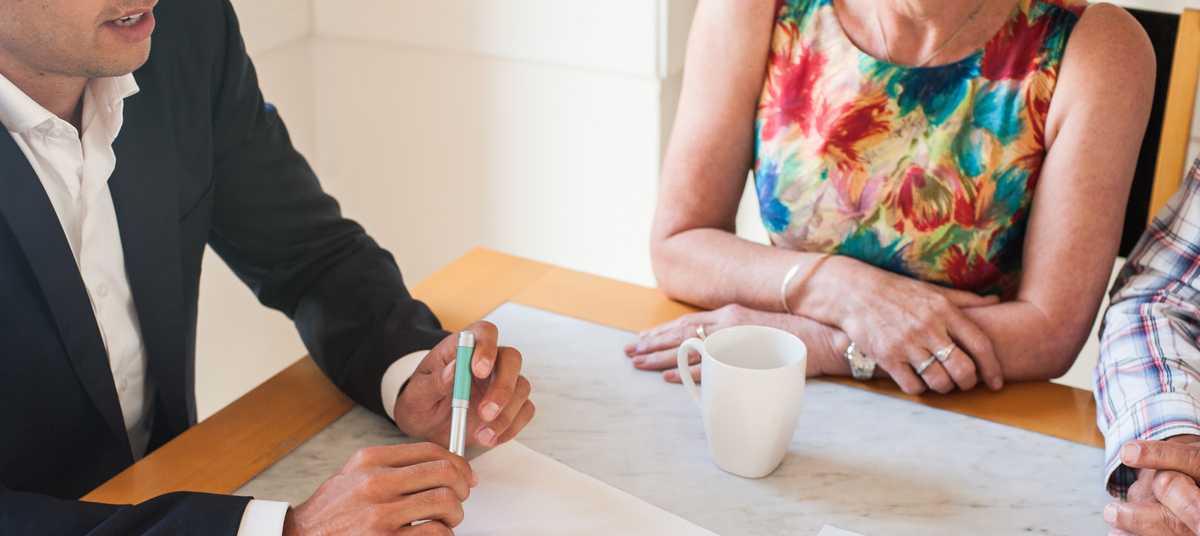 Couple d'acheteur et agent immobilier pour la signature du compromis de vente